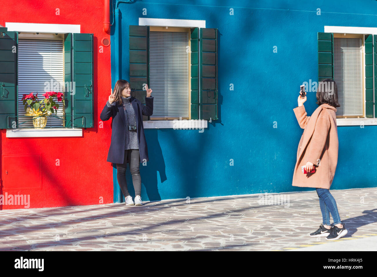 Female tourist poses for a photograph in front of bright blue and red houses at Burano - bright colors of Burano, Stock Photo