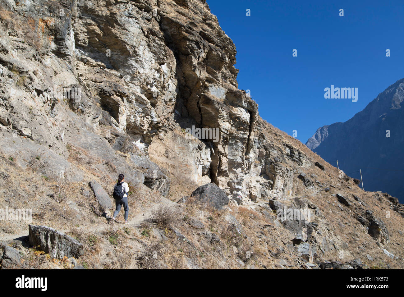 Woman hiking in Tiger Leaping Gorge, Yunnan, China (MR) - Stock Image