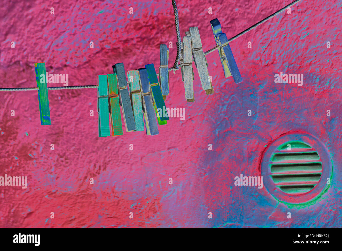Abstract of solarised clothes pegs on washing line with textured wall background - Stock Image