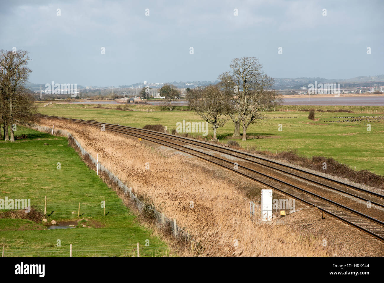 The River Exe at low tide seen from Starcross South Devon England UK With railway tracks heading west through farmland. - Stock Image