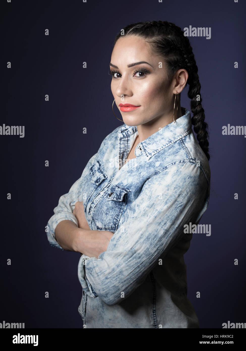 Hispanic woman with ponytails and denim shirt - Stock Image