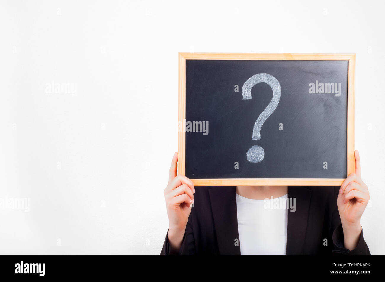 Woman holding chalkboard with question mark on it before face. - Stock Image