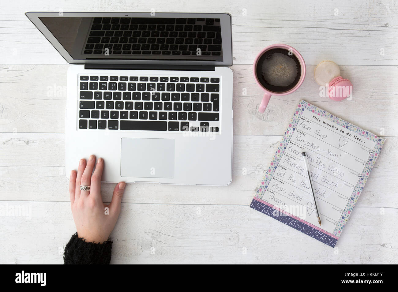 Flatlay overhead view of laptop with coffee macaroons and to do list - Stock Image
