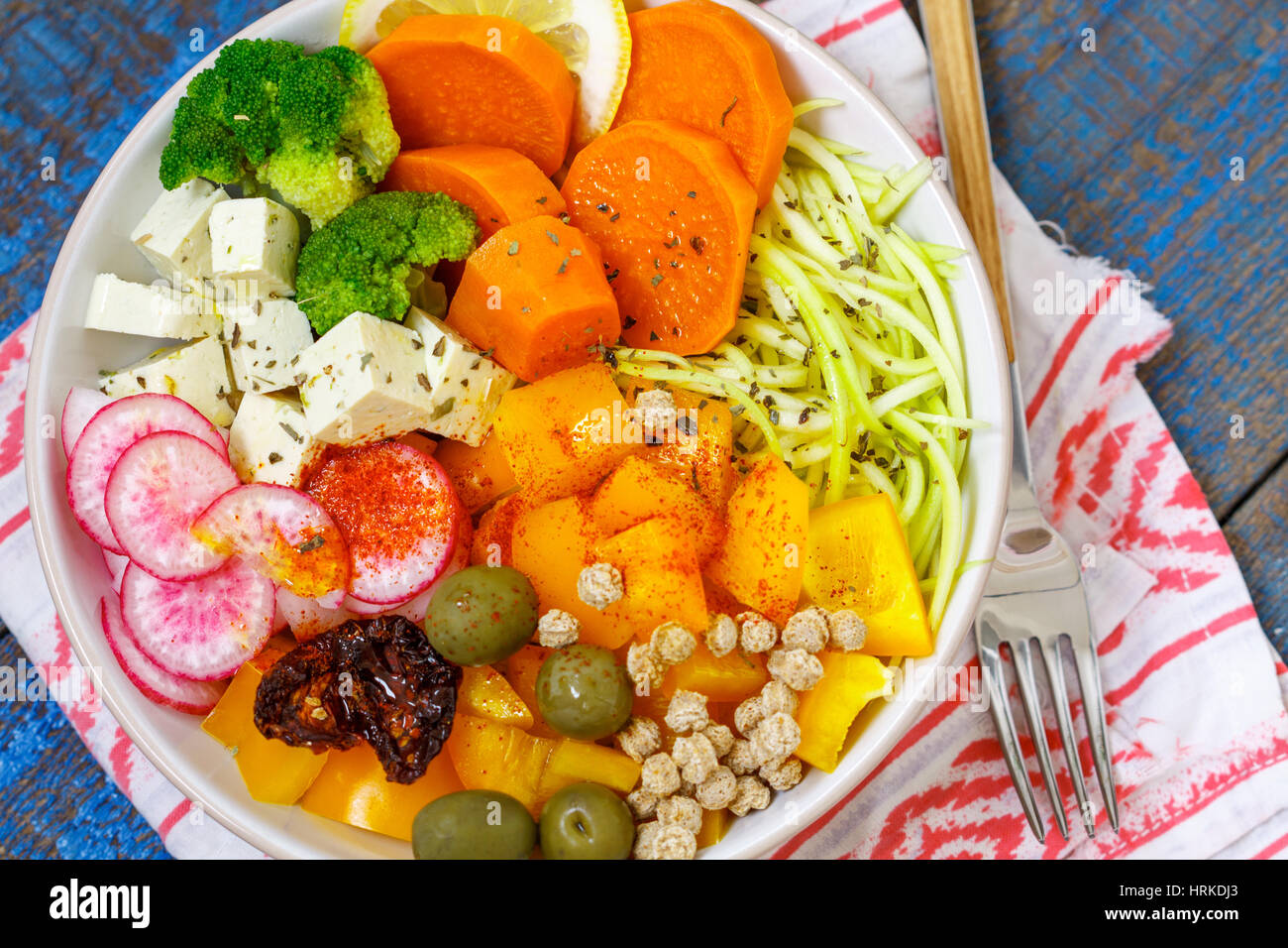 Vegan Buddha bowl - zucchini pasta, sweet potatoes, tofu with vegetables. Love for a healthy vegan food concept - Stock Image
