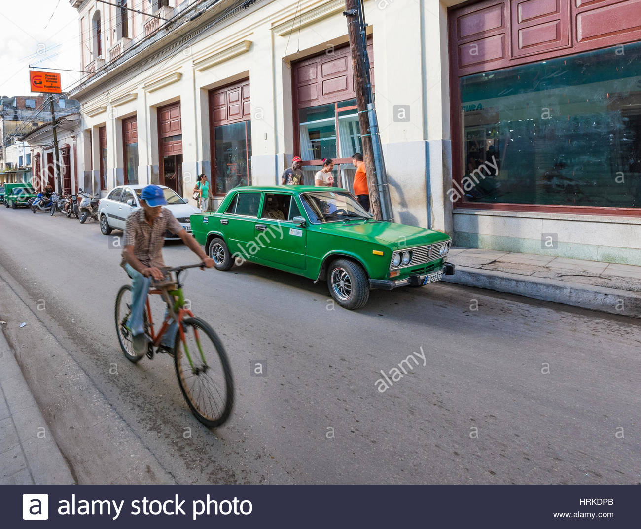 Senior riding bicycle in Colon Street. Cuban transportation and lifestyle during the Revolutionary period. - Stock Image