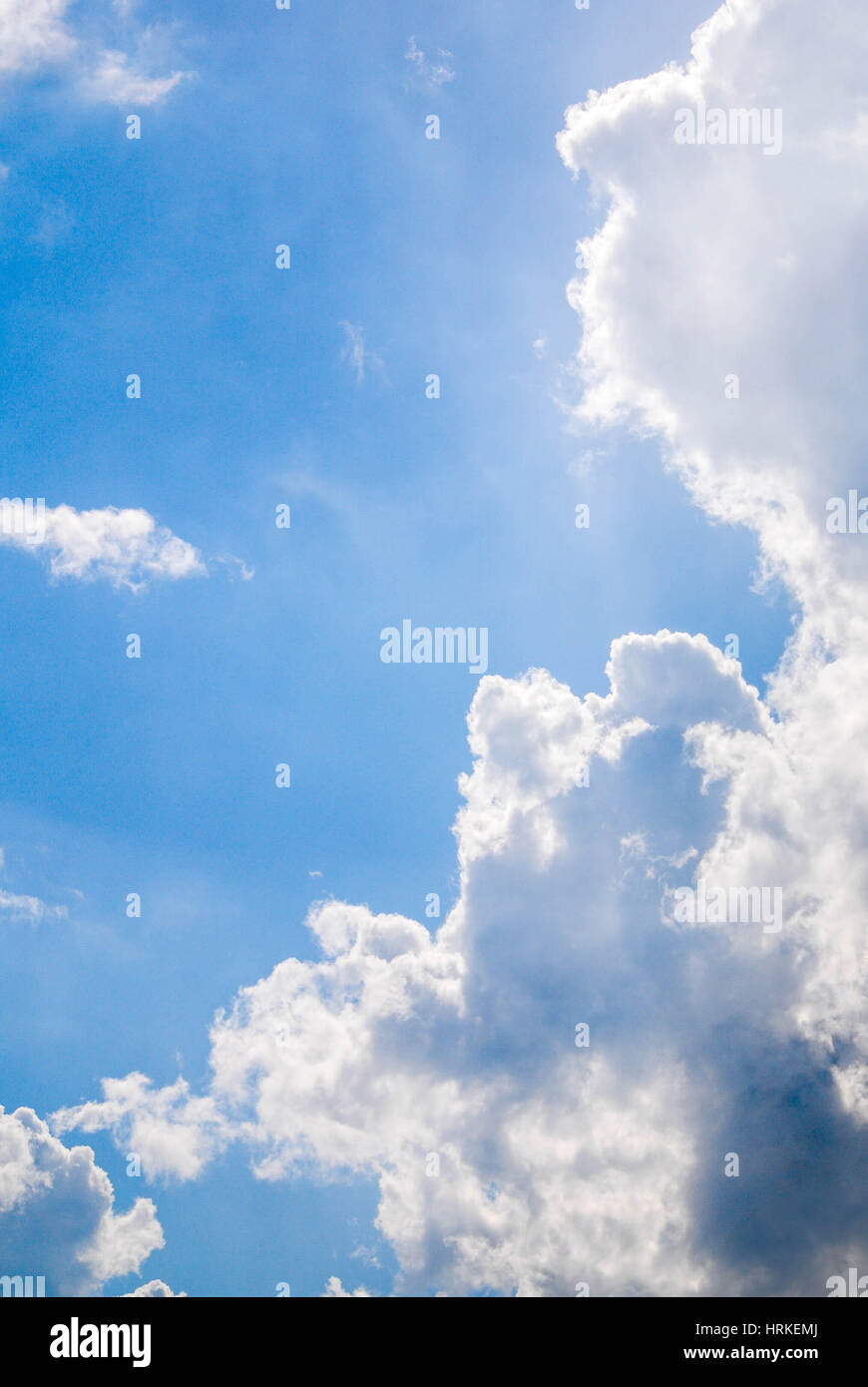 Fluffy white clouds against a bright blue sky on a summers day in England - Stock Image