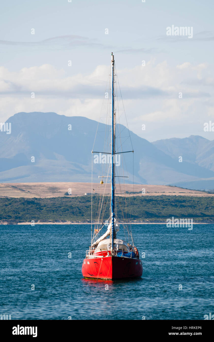 A red yacht on a calm ocean in Mossel Bay, South Africa - Stock Image