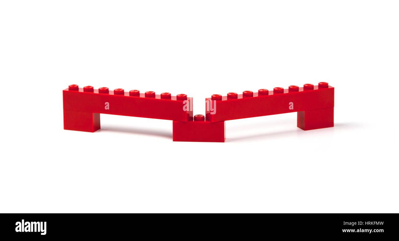 Lego brick construction, bridge, viaduct, barrier, etc. of interlocking red Lego bricks on white. - Stock Image
