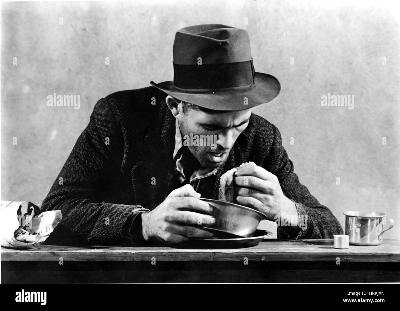 Homeless Man Eating in a Soup Kitchen - Stock Image