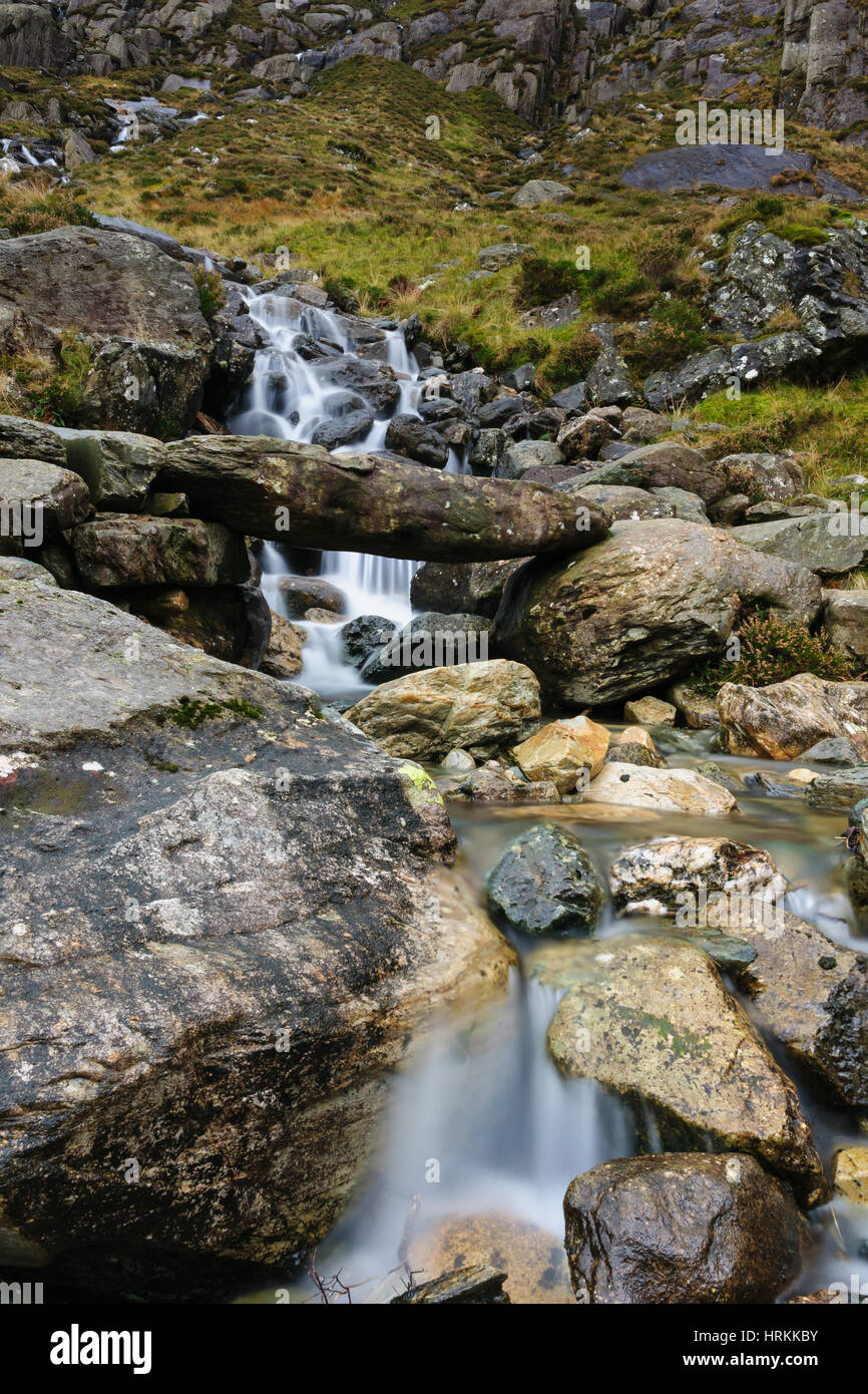 A small mountain stream and primitive stone bridge on the Cwm Idwal track in the Snowdonia National Park in North - Stock Image