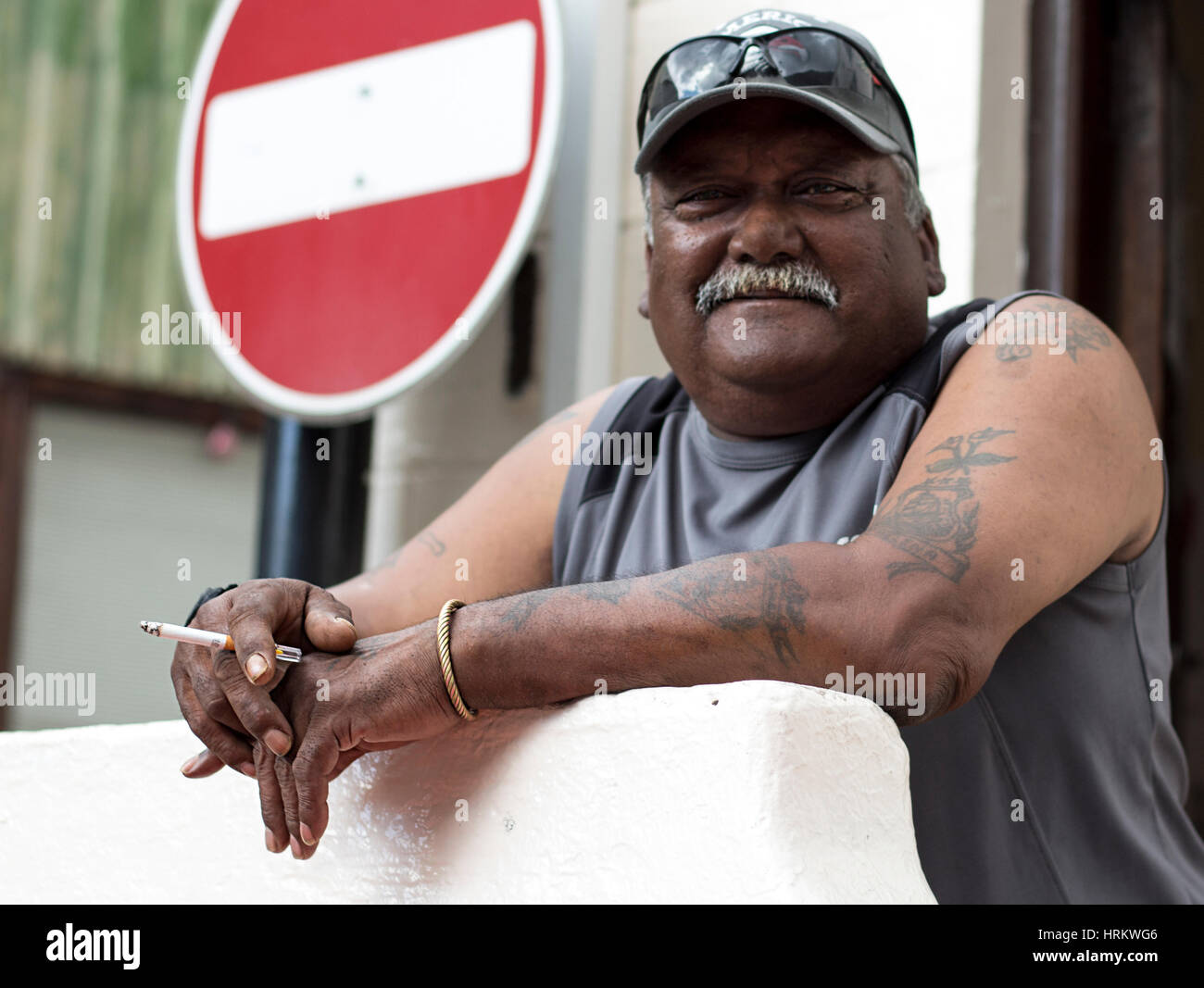 Man with moustache holding a cigarette. A wrong way sign is behind him. - Stock Image