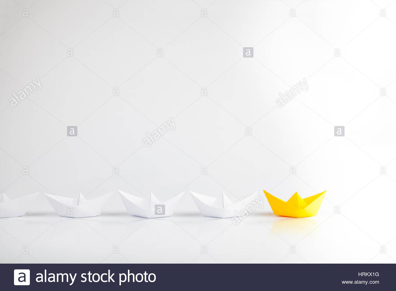 Leadership concepts with yellow paper ship leading among white - Stock Image