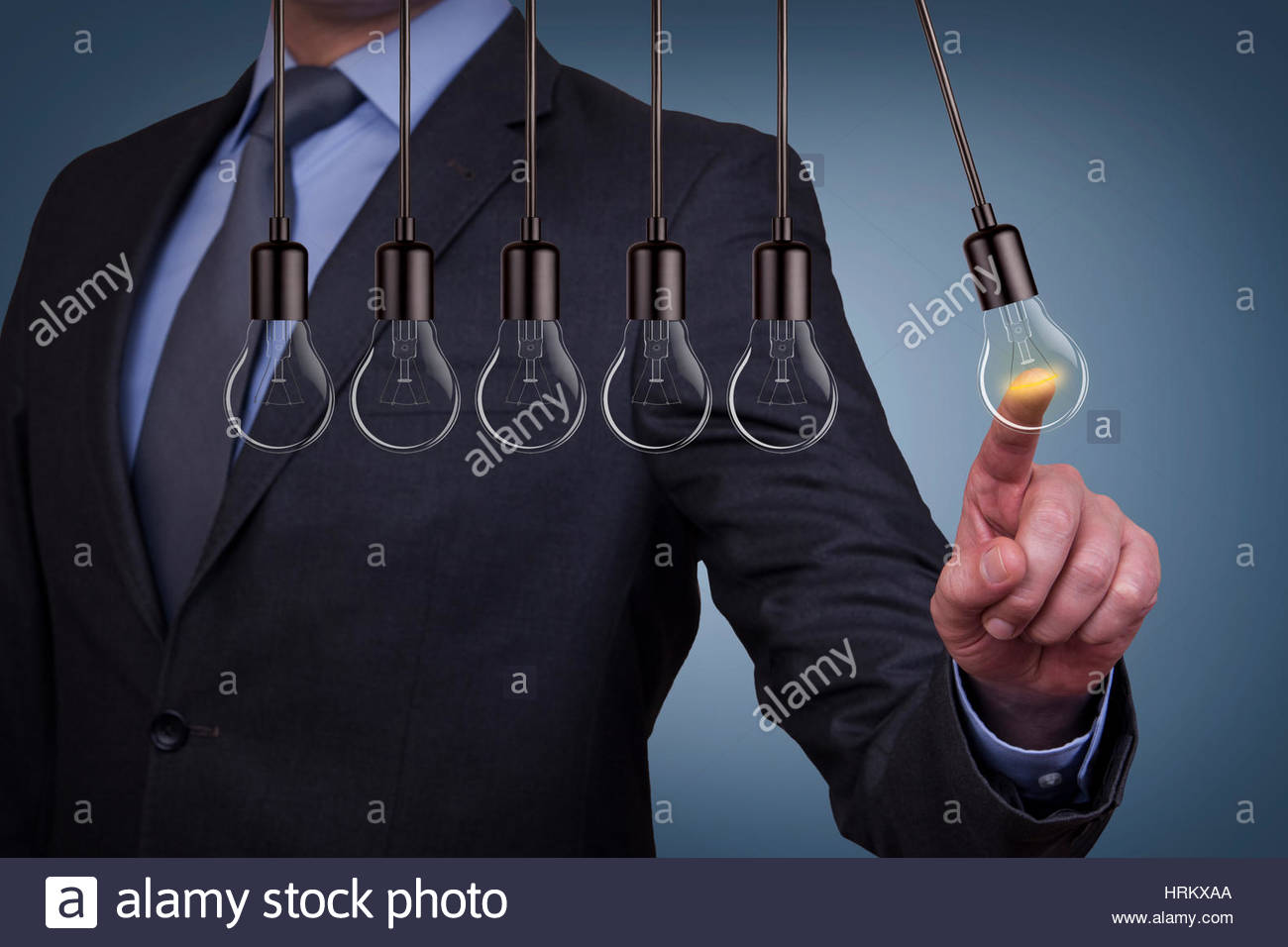 Innovation Concepts Human Hand Touching Light Bulb - Stock Image