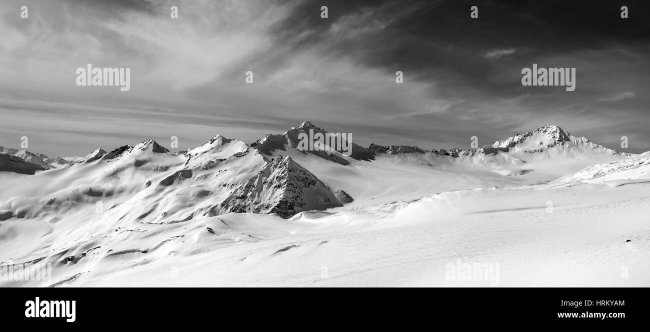 Black and white panorama of snow mountains in winter evening. Caucasus Mountains, Elbrus Region. View from off-piste - Stock Image