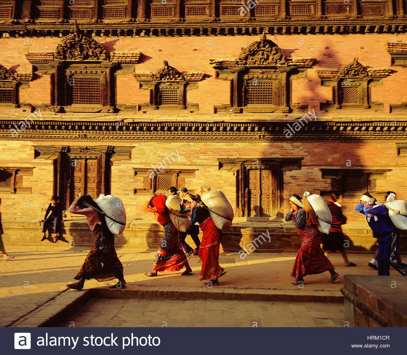 People carrying rice bags near the Fifty-Five Windows Palace, Bhaktapur, Nepal, Asia, - Stock Image