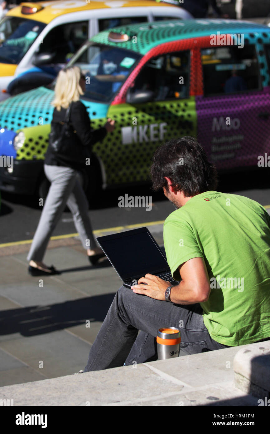 A male sits on steps in a London Street working on his laptop. Stock Photo