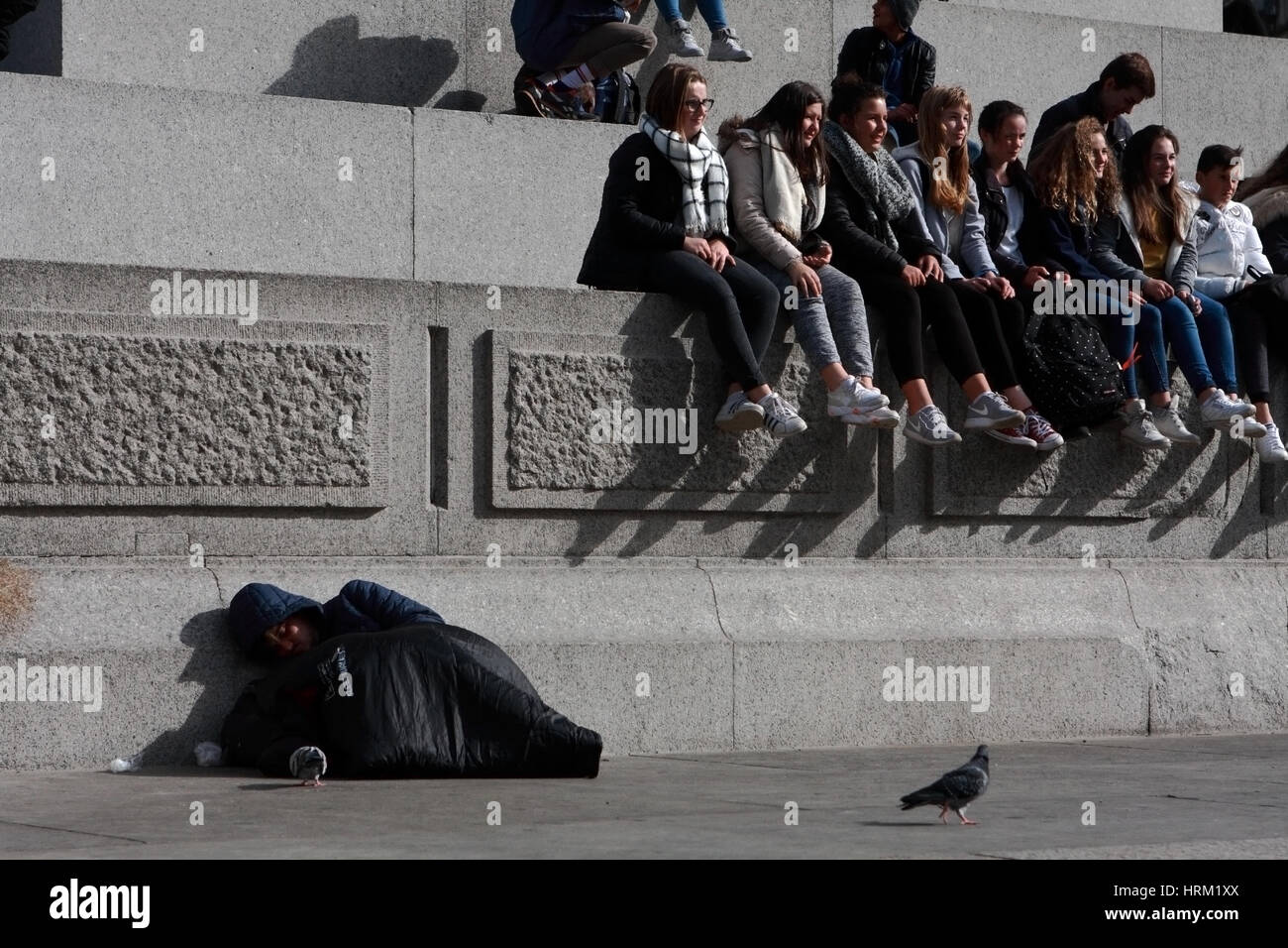 Tourists sitting on the base of Nelson's Column in Trafalgar Square - a homeless person in a sleeping bag resting Stock Photo
