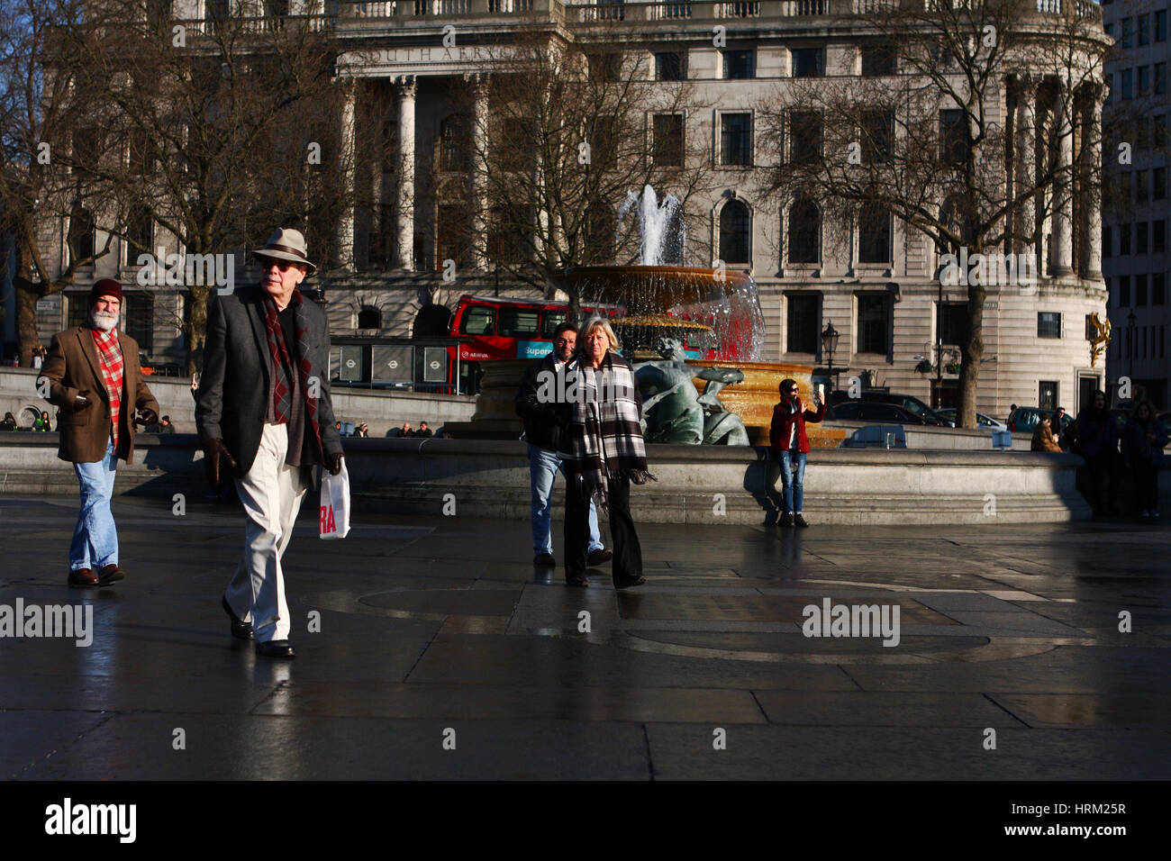 People walking in Trafalgar Square in winter sunshine Stock Photo