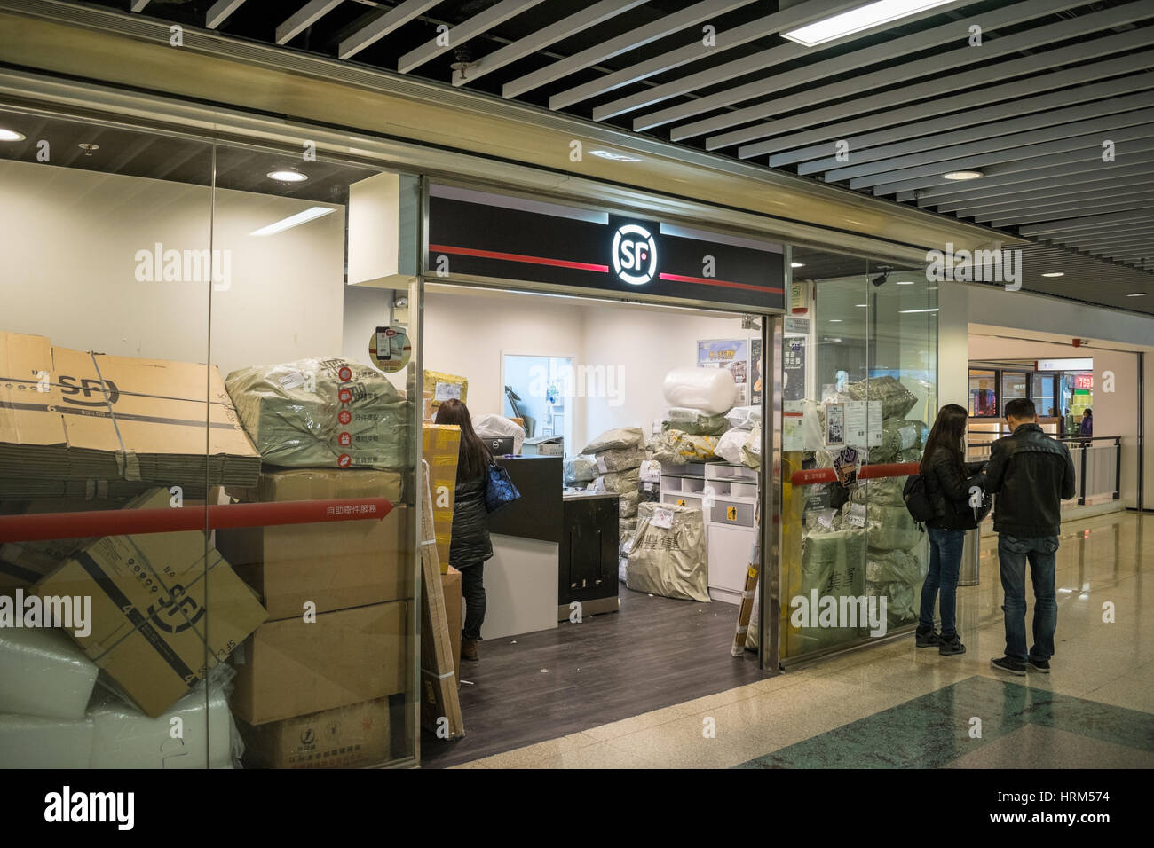 Chinese parcel delivery SF Express branch with parcels stacked in office in Hong Kong - Stock Image