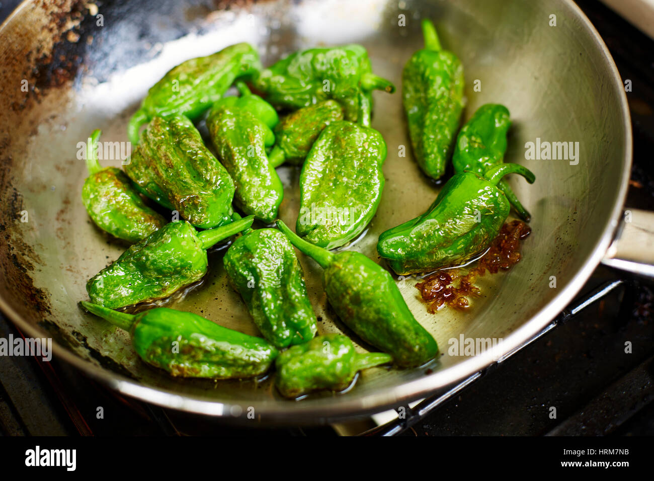 Fried Spanish padron peppers, Famous for being a bit like Russian roulette some are cool while other are very spicy - Stock Image