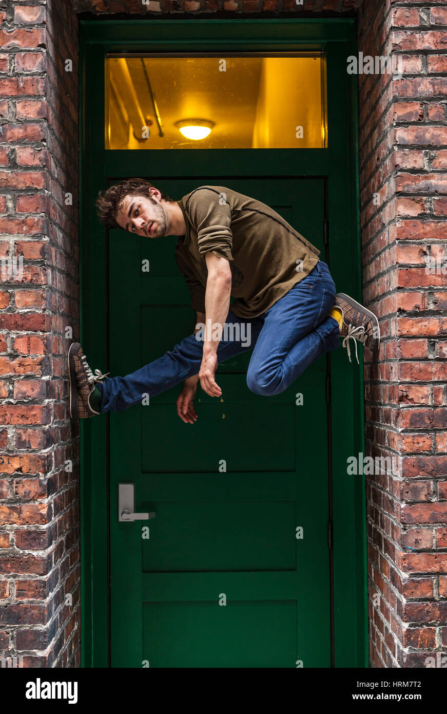 A portrait of a young man wedged up into a narrow doorway. - Stock Image