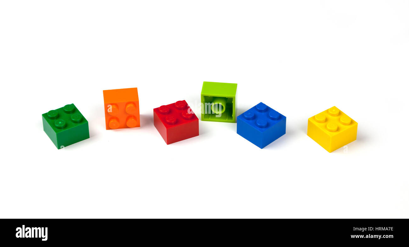 Green, orange, red, blue, yellow Lego bricks or pieces 2 by 2, 2x2 on white. - Stock Image