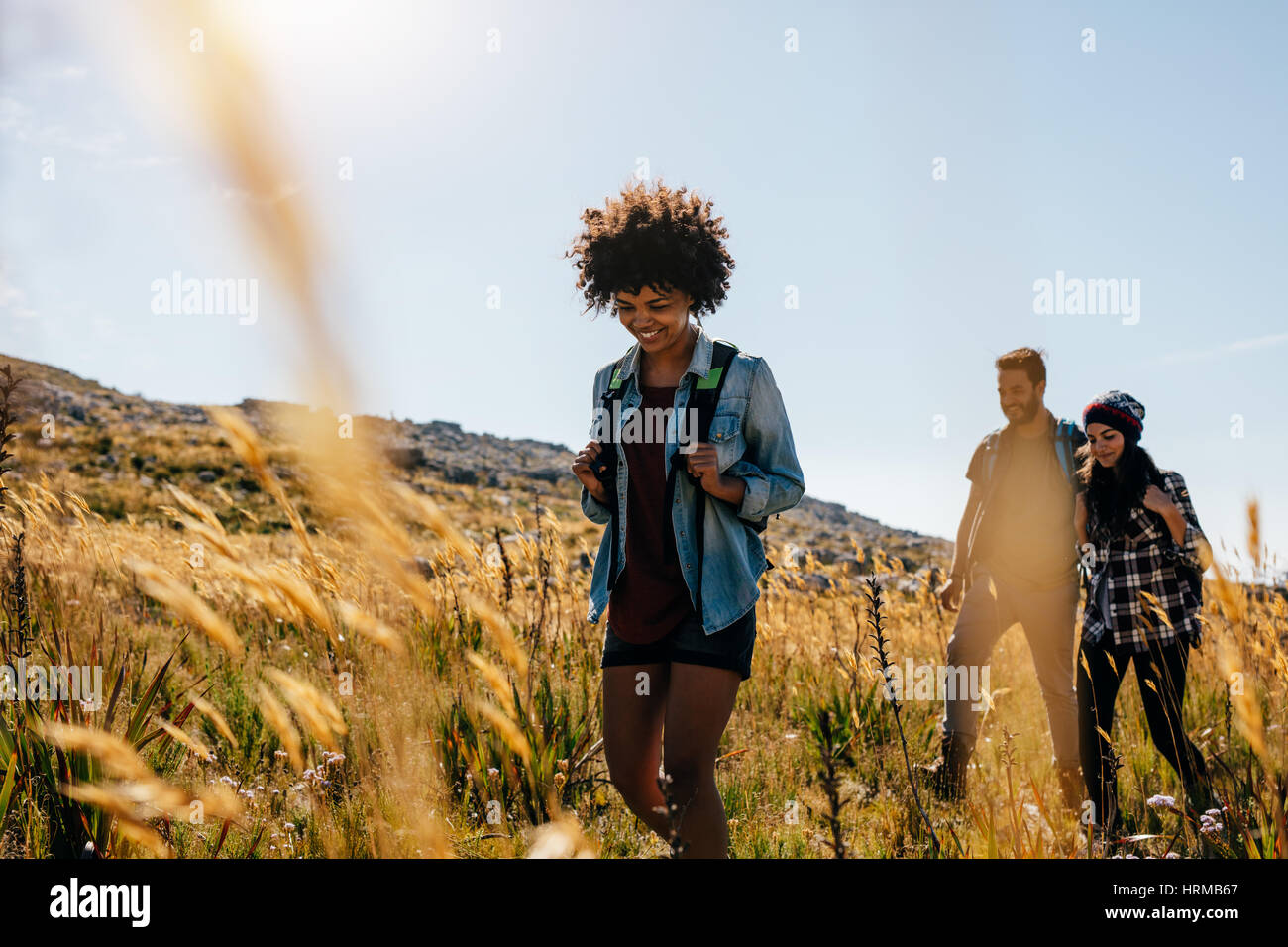 Group of people hiking in countryside. Young women and men on mountain hike. - Stock Image