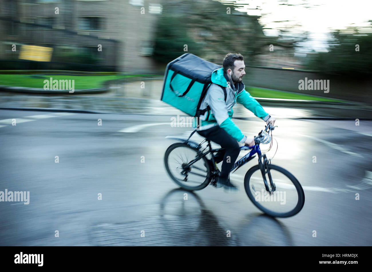 73f7d884134 A Deliveroo food delivery courier rushes through central Cambridge UK -  Stock Image
