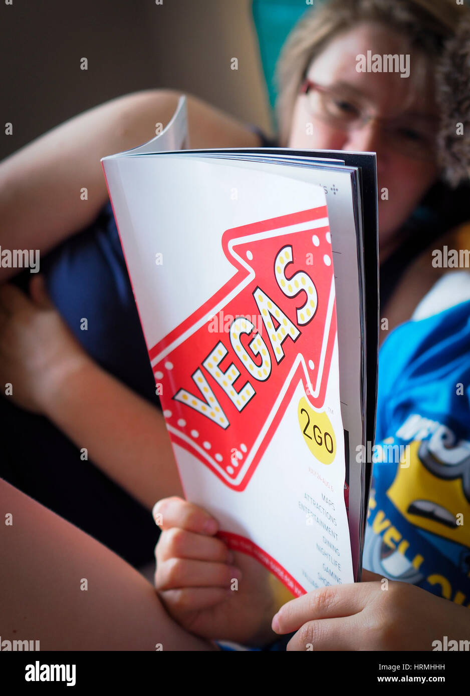 Las Vegas tourists prepare for a night out by checking the city programme in the 'Vegas2Go' magazine - Stock Image