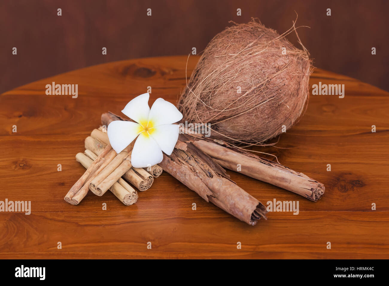 Whole coconut, cinnamon sticks and flower on wooden brown table. Close-up - Stock Image