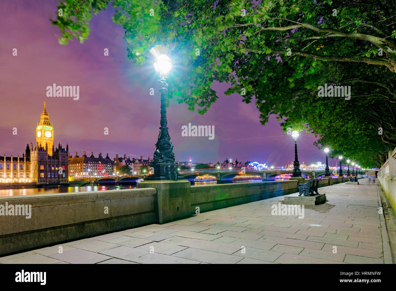 Riverside path at night with view of London - Stock Image