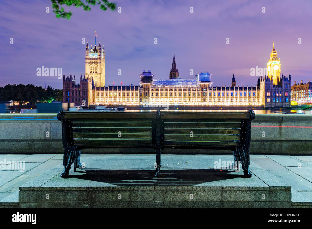 Bench at night with Houses of Parliament in the distance - Stock Image