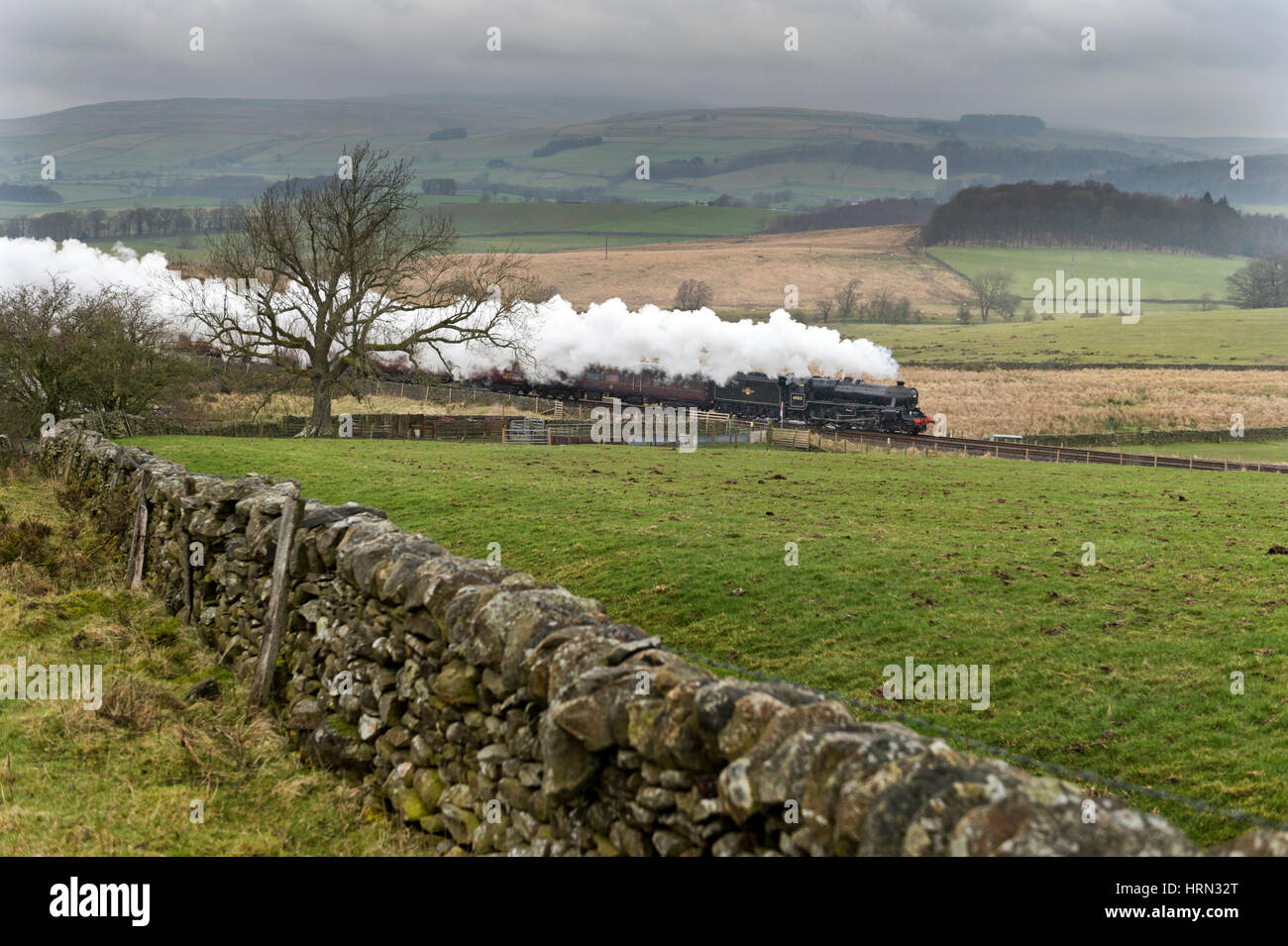 Yorkshire Dales, UK. 3rd Mar, 2017. Under a raincloud a Black 5 steam locomotive No.45212 on a test run from Steamtown; - Stock Image