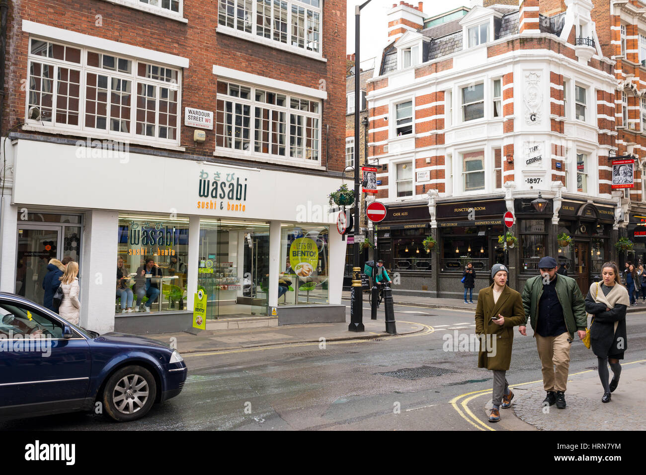 People walking in Wardour street, Soho in front of a local branch of the Japanese restaurant Wasabi. London, UK - Stock Image