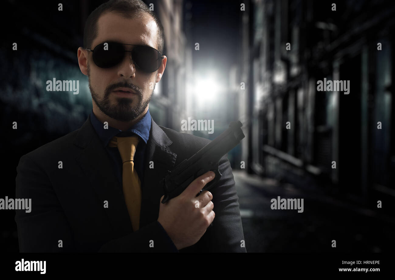 Mafia man or racketeer holds pistol in hands. - Stock Image