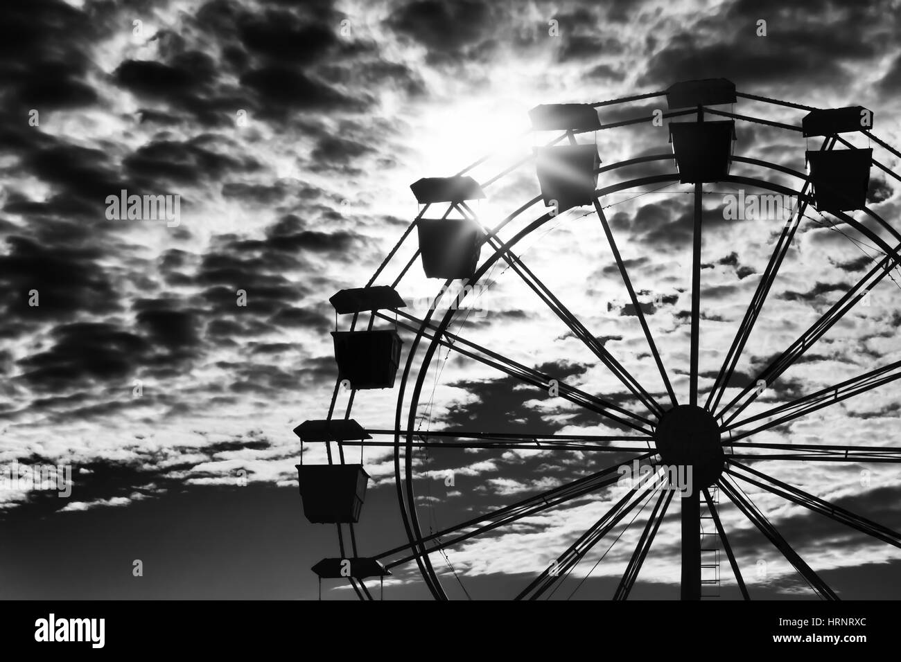 Ferris wheel silhouetted against an intense sky. - Stock Image