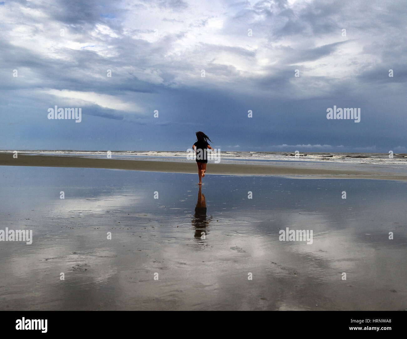 Tween girl wearing a bathing suit runs toward the waves on the beach at Kiawah Island, South Carolina. It is a stormy - Stock Image