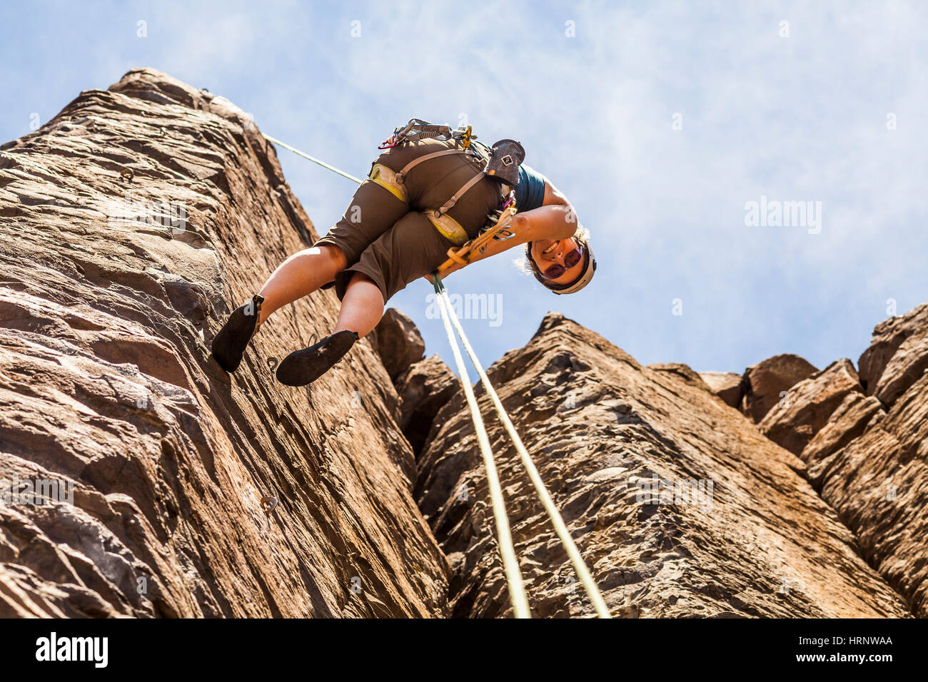 Looking up at a woman who is rappelling down from a rock climb at Frenchmans Coulee in Eastern Washington, USA. Stock Photo