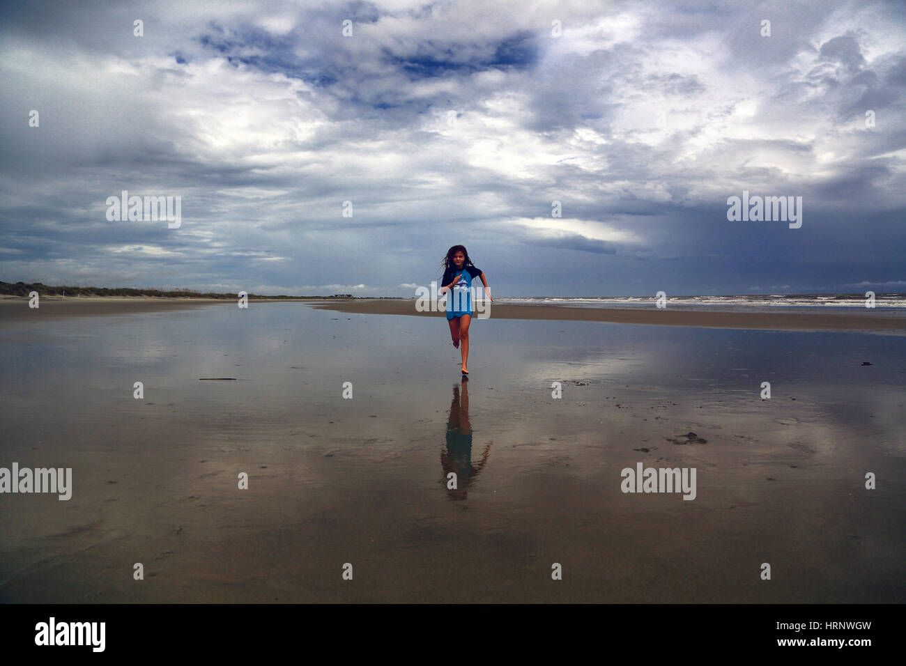 A tween girl wearing a bathing suit runs on the beach at low tide on Kiawah Island, South Carolina. A stormy sky - Stock Image