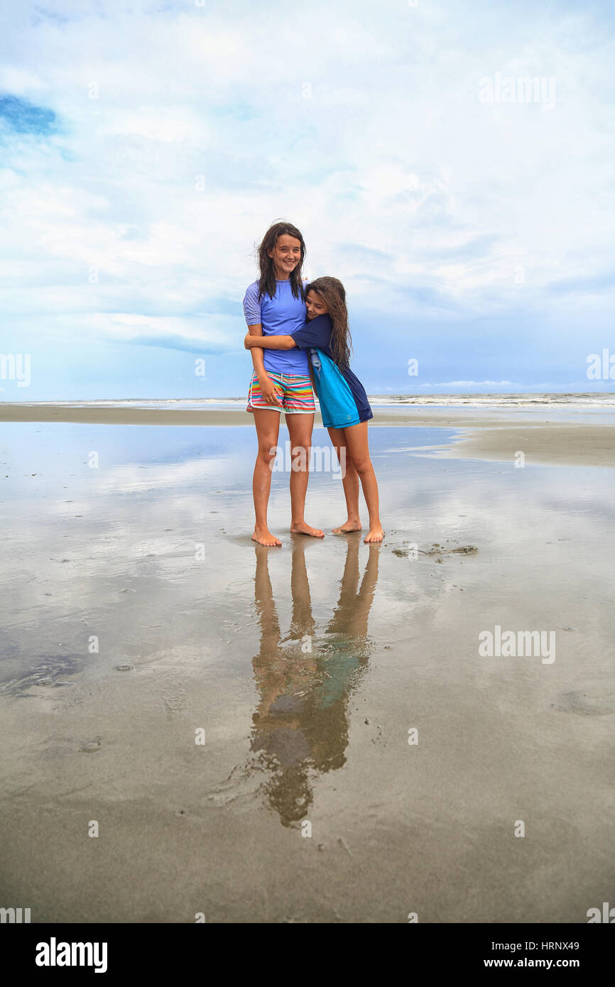 Two brunette tween sisters hug on the beach on a cloudy day. They are wearing rash guards and board shorts. - Stock Image