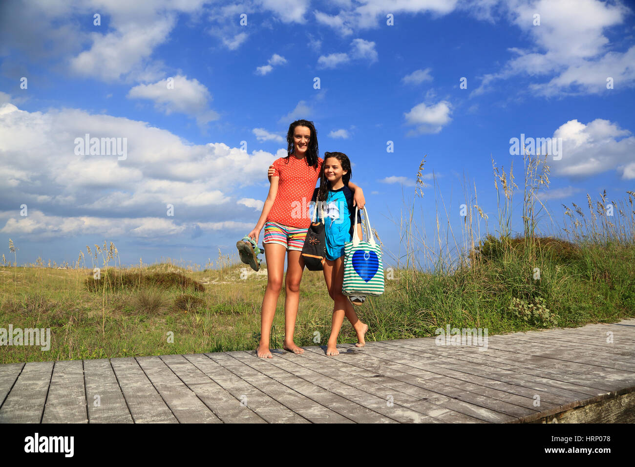 Two brunette girls stand with their arms around each other on a beach boardwalk on the dunes on a sunny day. They - Stock Image