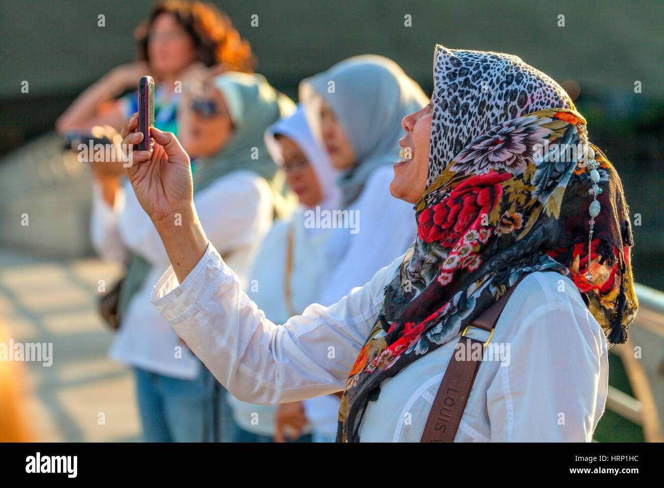 woman, Tourist with scarf, photographed The Merlion, landmark of the metropolis of Singapore, downtown skyline, - Stock Image