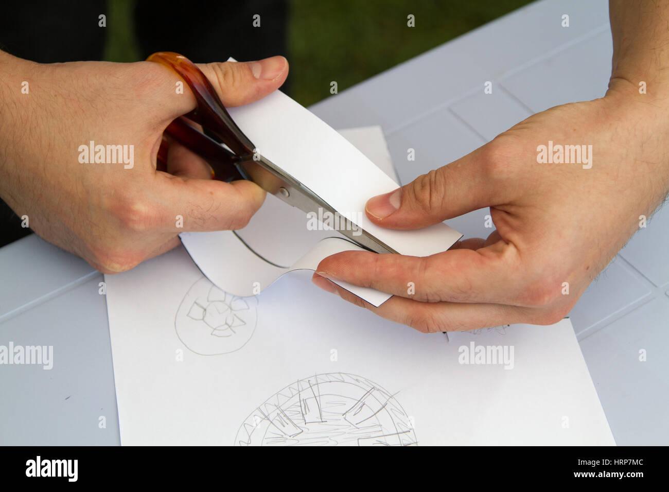 cutting a sheet of green paper using metallic scissors - Stock Image