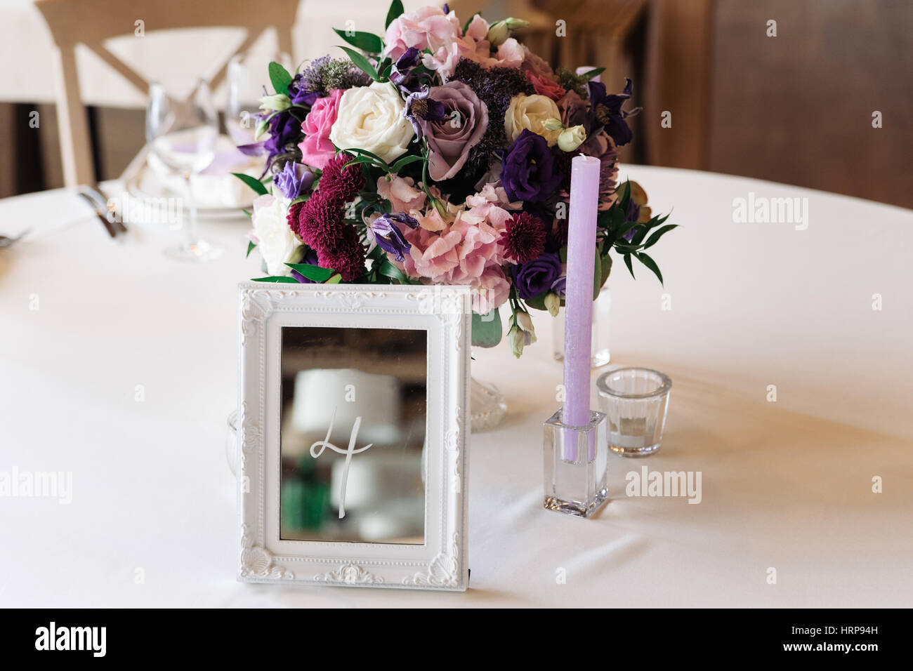 Wedding table with candles, flowers and sign number - Stock Image