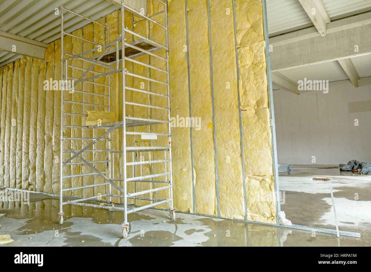 Mobile scaffold is used to complete dividing wall with thermal insulation, mineral wool. - Stock Image