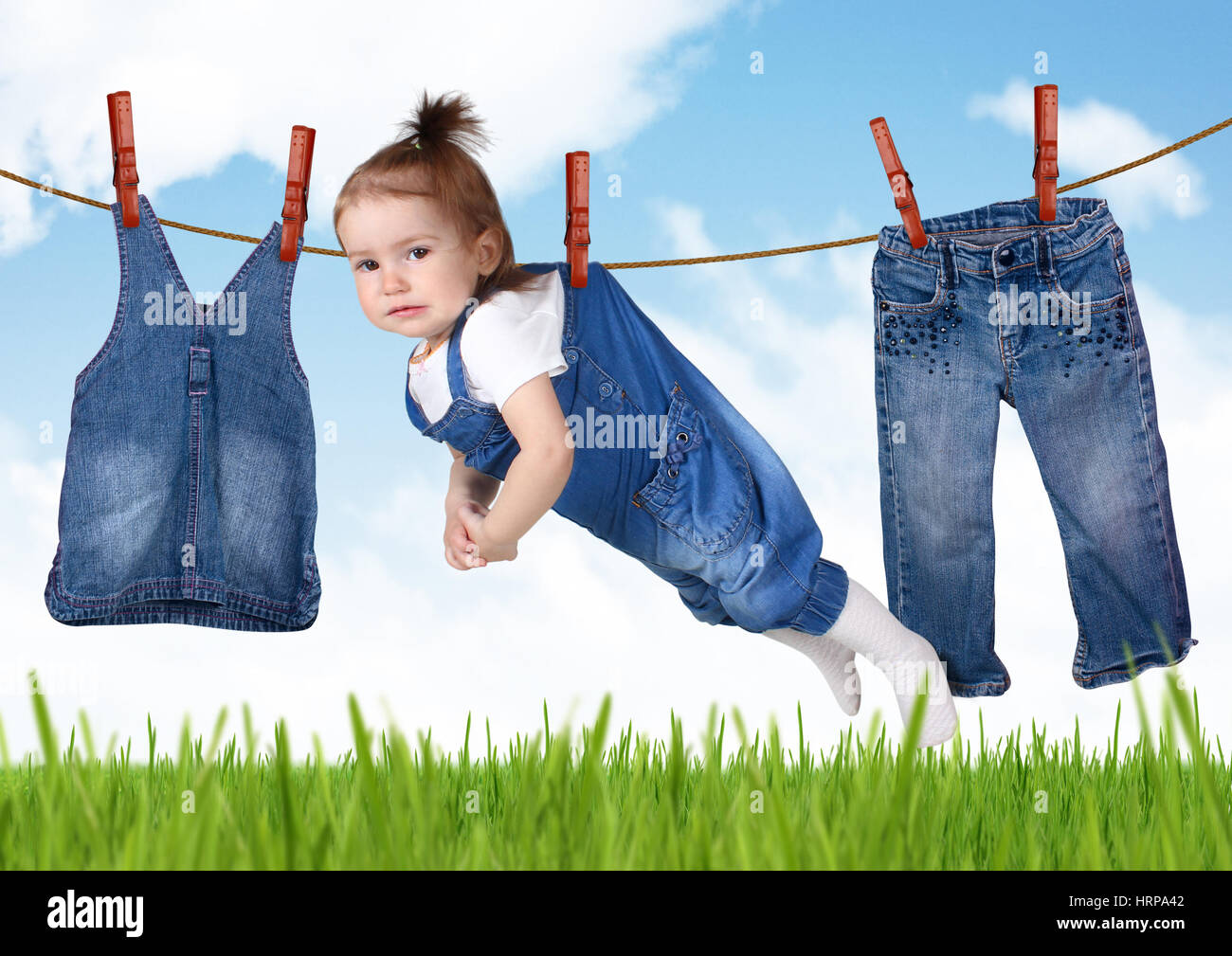 confused housework concept, Funny child hanging on clothesline - Stock Image