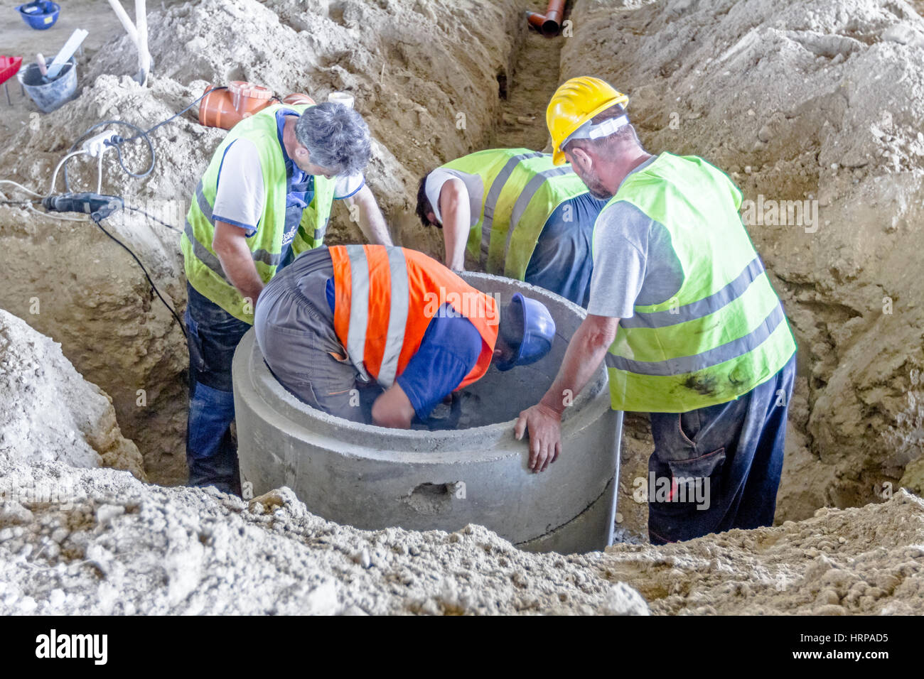 Work is in progress. Construction workers are assembly new concrete manhole on building site. - Stock Image