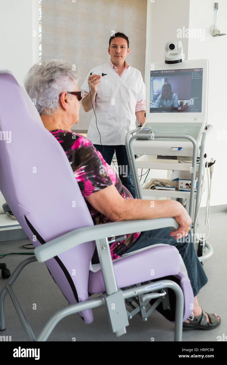 Medical consultation in a telemedicine practice in rural area, Patient assisted by a nurse for remote consultation - Stock Image