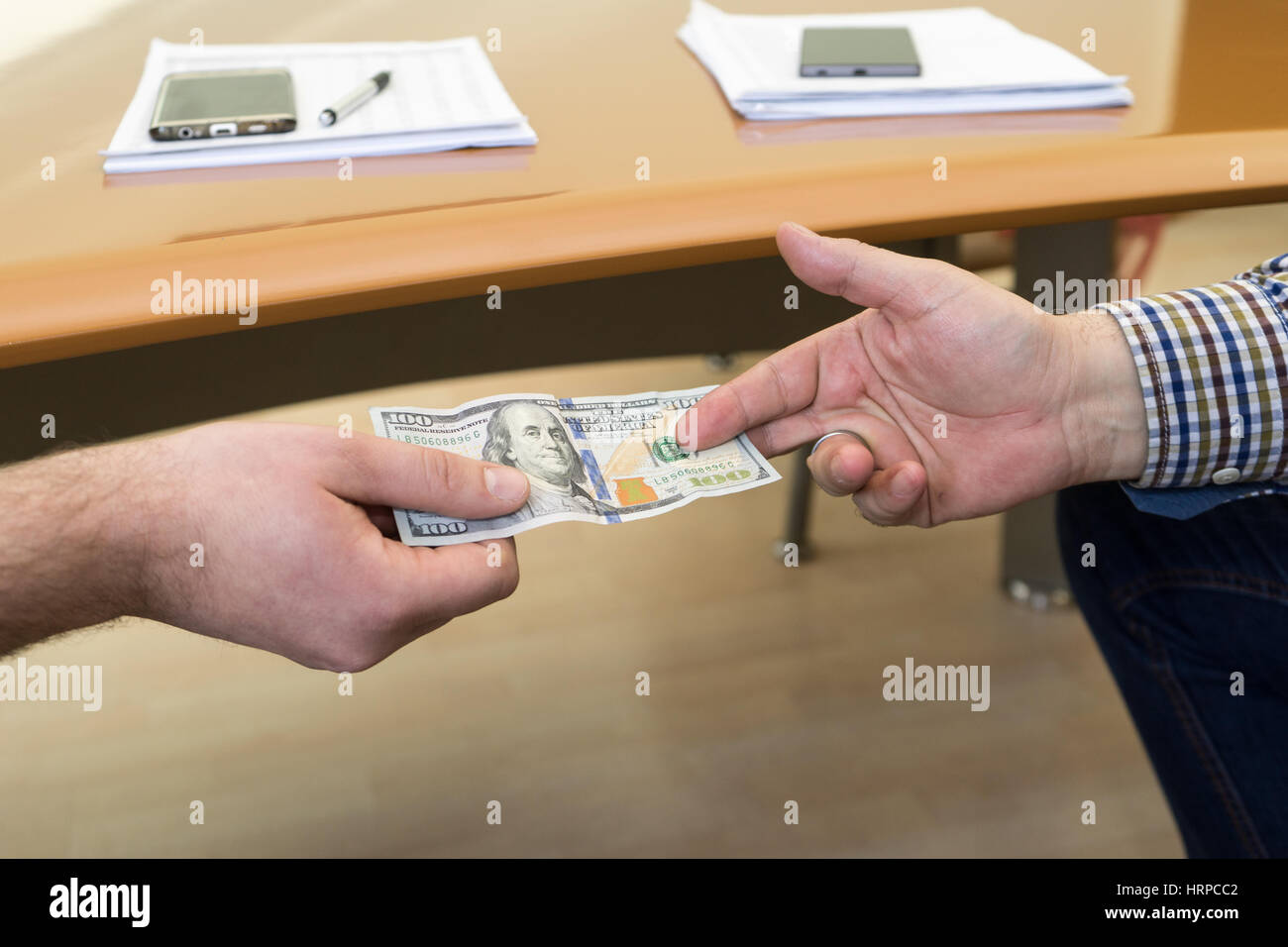 Man offering of hundred dollar bill. Hands close up. Corruption concept.  United States Dollars (or USD). - Stock Image