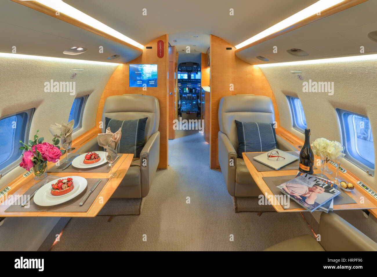 Interior view of Bombardier CL-604 Challenger executive jet, with tables set with plated food, looking towards the - Stock Image